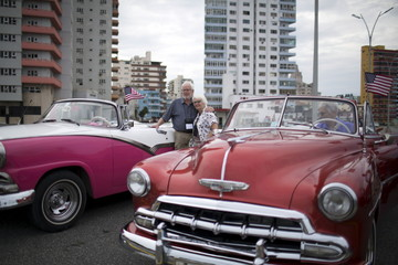 A U.S. citizen poses for photos as he enjoys a ride in a vintage car at the seafront Malecon during a cultural exchange trip in Havana