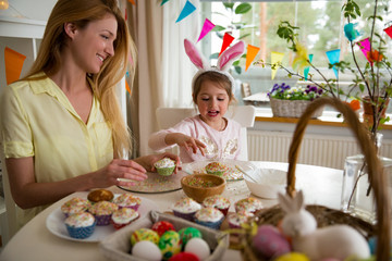 Mother and daughter celebrating Easter, cooking cupcakes, covering with glaze. Happy family holiday. Cute little girl in bunny ears.
