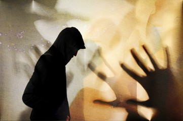 Vintage silhouette of young man with hooded sweatshirt and shadows of many hands. Threat concept.