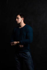 Handsome tough guy on a black background. Brawn. Sweater. Jeans. Force. Masculinity.