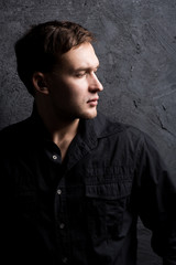 Portrait of a handsome muscular guy on a black background in a shirt. Black shirt. Profile. Force.