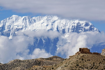 Ruins of an ancient fortress against the backdrop of the Annapurna mountain range. Upper Mustang. Nepal.