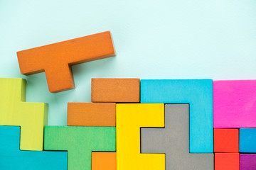 Different colorful shapes wooden blocks on blue background, flat lay. Geometric shapes in different colors, top view. Concept of creative, logical thinking or problem solving. Copy space.