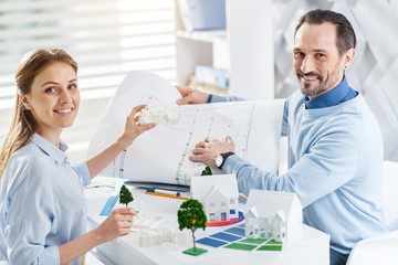 Happy co-workers. Good-looking exuberant bearded man smiling and holding a drawing and working with his colleague holding a miniature house while sitting at the table