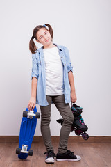 Teenager girl with skateboard and rollers posing at home to the camera