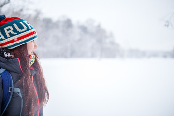 Portrait of side view of woman with long hair in winter forest