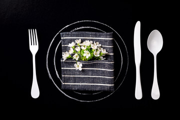 Spring table setting with white flowers on a black background