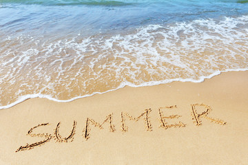 "The word ""Summer"" written on the sand at the edge of the sea."