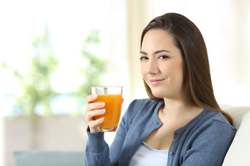 Serious woman holding a glass of orange juice