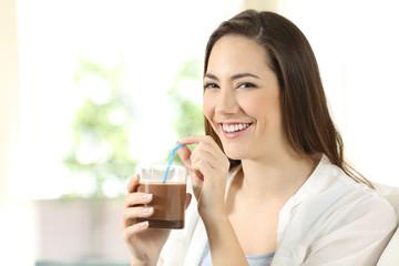Woman drinking cocoa shake looking at camera