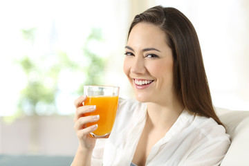 Woman holding a glass of orange juice at home