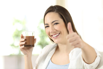 Woman holding a cocoa drink looking at camera
