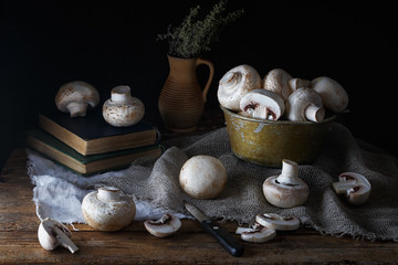 Mushrooms champignons on an old rustic wooden table on a dark background. Low key. Focus concept. .Vintage style....