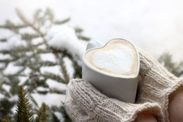 warming moments of winter holidays/ frothy coffee in a mug shaped like a heart, in the hands that are dressed in mittens