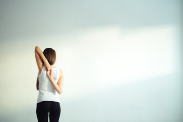 Rear view of fit woman doing gomukhasana in yoga class. Fitness female holding hands behind their back and stretching