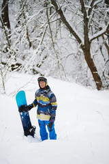 Happy snowboarder stands in the winter forest after snowfall