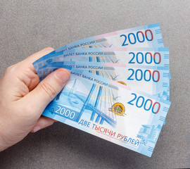 new Russian banknotes denominated in 2000 rubles in male hands close-up on a gray background with copy space, top view