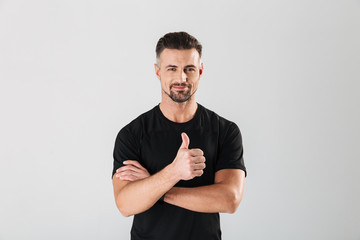 Strong sportsman showing thumbs up. Wall mural