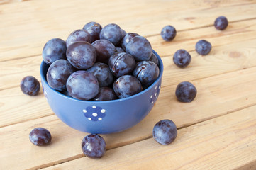 Plums in plate on wooden table