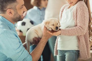 father giving his daughter adorable labrador puppy Wall mural