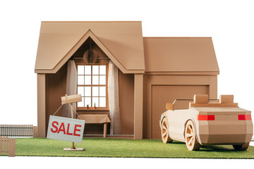 cardboard house and car with sign sale isolated on white