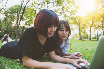 Young asian women lying on grass and using laptop and typing. Girls hands on keyboard. Distance learning concept. Happy hipster young asian women working on laptop in park. Student studying outdoors.
