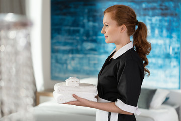 Professional housemaid holding towels