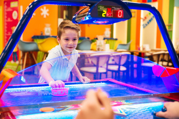 Happy little boy playing air hockey with his dad