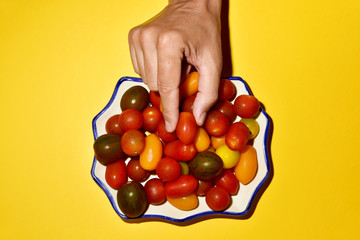 man picking a cherry tomato from a plate