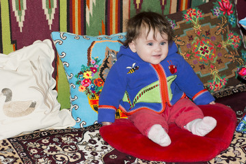Amazing little girl sitting in bed on a bed with embroidered pillows