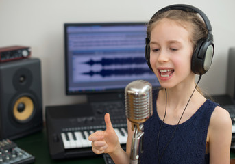 Little girl singing a song in home recording studio.