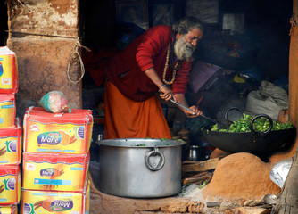 A Hindu holy man, or sadhu, cooks spinach at the premises of Pashupatinath Temple on the eve of Shivaratri festival in Kathmandu