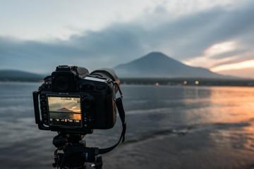夕方の山中湖にて富士山を撮影中の一眼レフカメラ