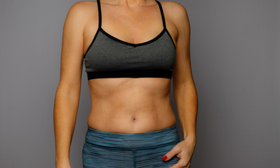 Woman Showing Belly Bulge on A Gray Background
