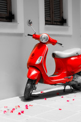 Red motor scooter. Rose petals, sunny day and black-and-white photography. Ancient street of Crete.