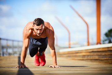 Athletic man doing push-ups during an outdoors workout