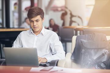 Youg handsome businessman using laptop