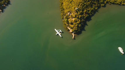 Aerial view: White Seaplane parked in the sea bay of the tropical island. Hydroplane in the lagoon and coastline. Philippines,Palawan, Busuanga. Travel concept