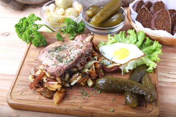 Fried pork with potatoes, egg and pickle cucumber on a wooden board