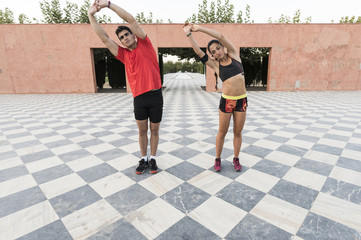 Young couple of athletes train in park with chess floor