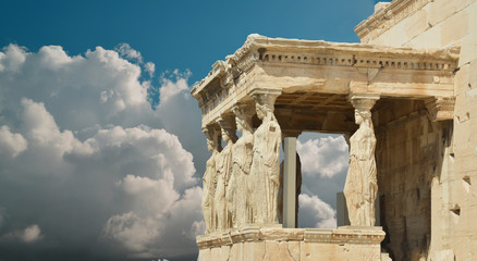 Wall Mural - caryatids in Athens Greece sky clouds