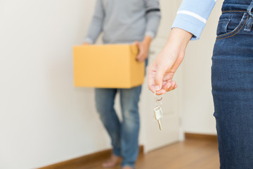 Close up of hand holding a key while a man holding a box to move in - buying new house concept