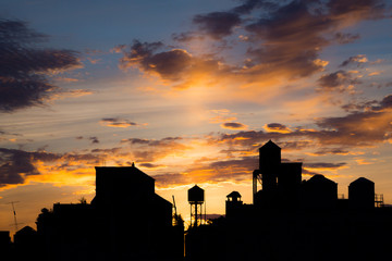 Silhouetted rooftops and water towers at sunset