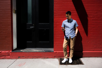 Man on his cellphone against a red wall