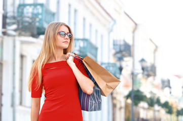 Young smiling woman with shoping bags look aside