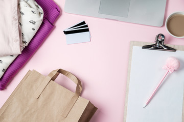 Online shopping background with computer, clothes, credit card on pink table. Flat lay, top view