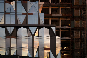 Partially constructed building reflecting the sunset