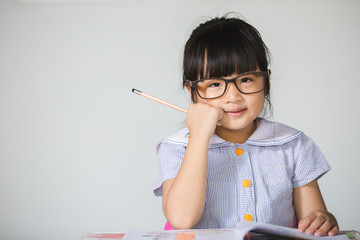 Little asian kid with glasses at home doing homework.