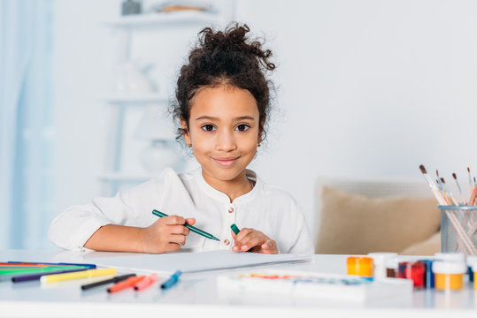 adorable african american kid drawing with felt pens and looking at camera at home