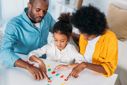 african american parents teaching daughter mathematics at home